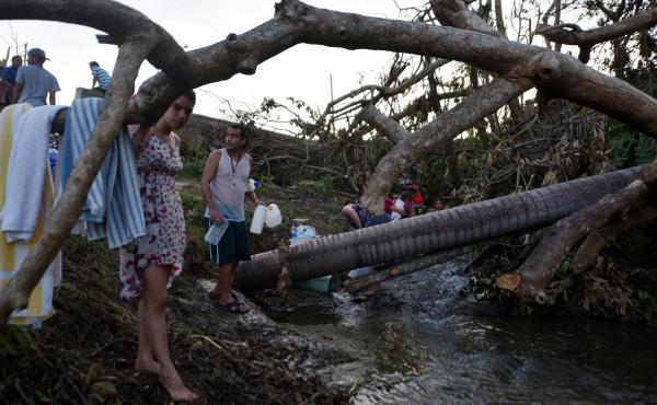 People carry water in bottles retrieved from a canal due to lack of water after Hurricane Maria, in Toa Alta, Puerto Rico, on Monday.