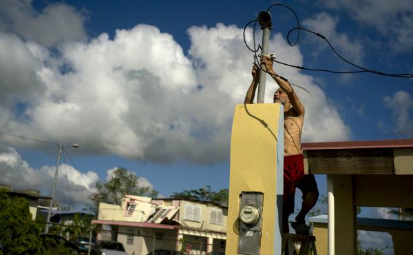 In a photograph taken in October, a resident tries to connect electrical lines downed by Hurricane Maria in preparation for when electricity is restored in Toa Baja, Puerto Rico.