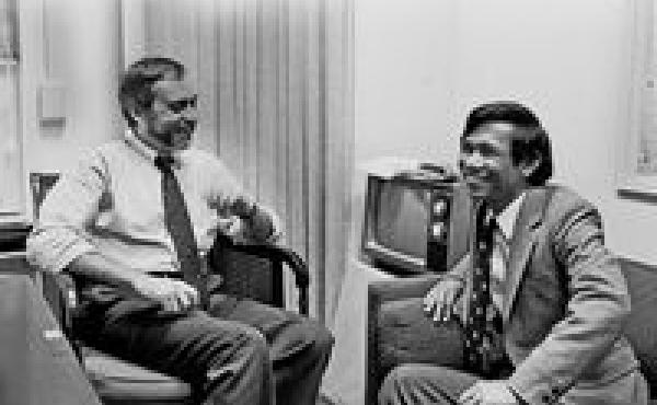 This image, courtesy of The New York Times, shows New York Times correspondent Sydney Schanberg talking with colleague Dith Pran in the Times office in New York in 1980.