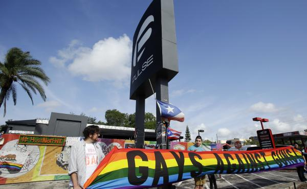 Activists hold a banner in front of the Pulse nightclub site on Thursday in Orlando, Fla.