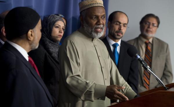 """Imam Johari Abdul-Malik (center), of Dar Al-Hijrah Islamic Center in Northern Virginia, speaks alongside other leaders of the Muslim community during a December 2015 news conference in Washington, D.C., about growing """"Islamophobia"""" in the United States."""