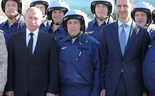 Russian President Vladimir Putin, left, and Syrian President Bashar Assad, right, pose for a photo with Russian military pilots at the Hemeimeem air base in Syria last December.
