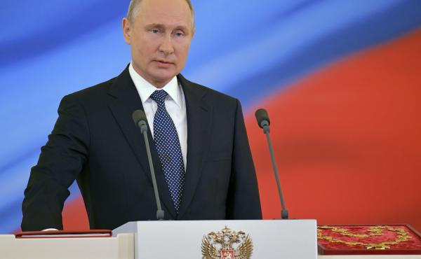 Vladimir Putin speaks with his hand on the Constitution during his inauguration ceremony as new Russia's president in the Grand Kremlin Palace in Moscow, Russia, on Monday.