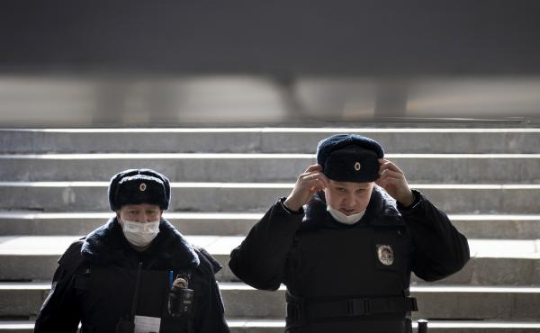 Russian police officers, wearing face masks to guard against the coronavirus, descend into a pedestrian underpass as they patrol to enforce a self-isolation regime in Moscow.