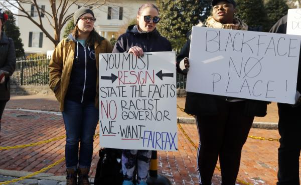 Demonstrators hold signs and chant in Richmond, Va., on Feb. 2. They were calling for the resignation of Gov. Ralph Northam after a racist photo on his medical school yearbook page came to light. He denies that he is in the photo but admits to once dressi