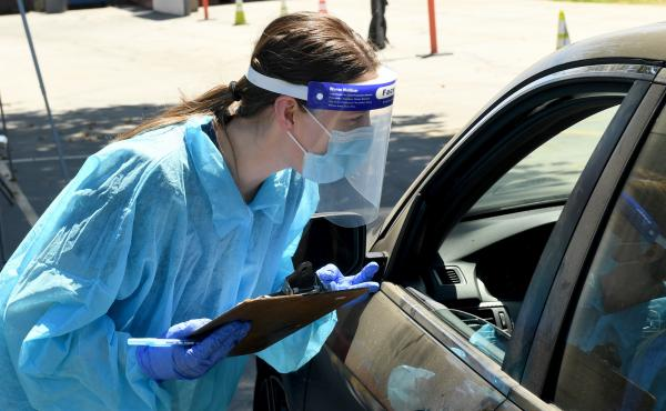 An urgent care worker wears personal protective equipment in drive-up testing for the coronavirus in the Los Angeles area. Leading public health scientists tell journalist Alexis Madrigal that widespread at-home testing could help contain the virus.