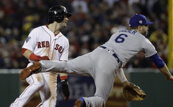 The Boston Red Sox's Andrew Benintendi's hard slide into the Los Angeles Dodgers' Danny Lehmann successfully breaks up a double-play Tuesday during the third inning of Game 1 of the World Series. Boston's Steve Pearce, who stayed on first after an officia