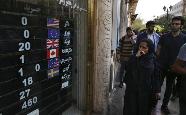 An exchange shop displays rates for various currencies in downtown Tehran last month. Iran is bracing for the restoration of U.S. sanctions on its vital oil industry set to take effect on Monday, as it grapples with an economic crisis that has sparked spo