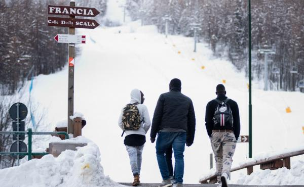 Migrants walk toward a snow-covered pass to cross the border from Italy to France, in January 2018 near Bardonecchia, Italian Alps.