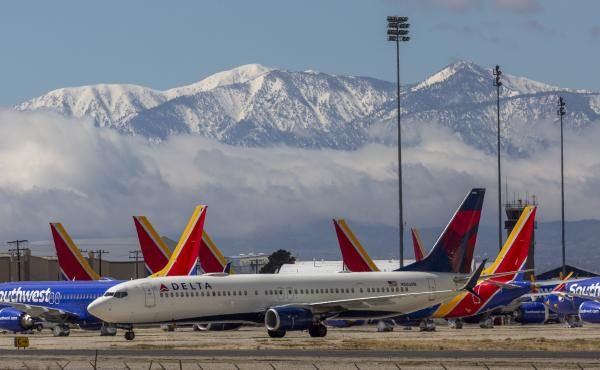 A Delta Air Lines jet taxis past Southwest Airlines jets to be parked with a growing number of jets at Southern California Logistics Airport on Tuesday in Victorville, Calif. Airlines around the world are scrambling to find places to park planes.