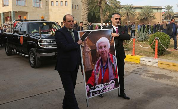 Mourners transport the flag-draped coffin of Iraqi archaeologist Lamia al-Gailani, seen in the poster, for burial during her funeral procession in the National Museum in Baghdad on Jan. 21. Iraq is mourning the loss of a beloved archaeologist who helped r