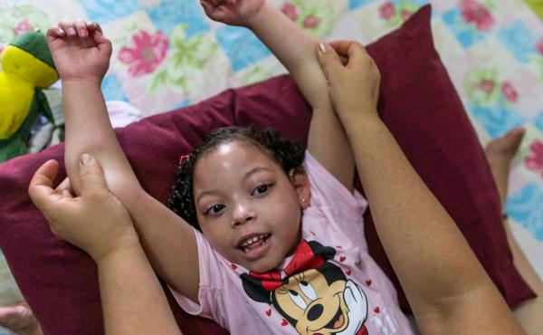Rochelle dos Santos helps her daughter with physical therapy. Many children with congenital Zika disorder are physically disabled.