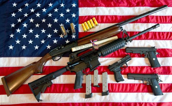 A Remington 20-gauge semi-automatic shotgun, a Colt AR-15 semi-automatic rifle, a Colt .45 semi-auto handgun, a Walther PK380 semi-auto handgun and ammunition set against an American flag.
