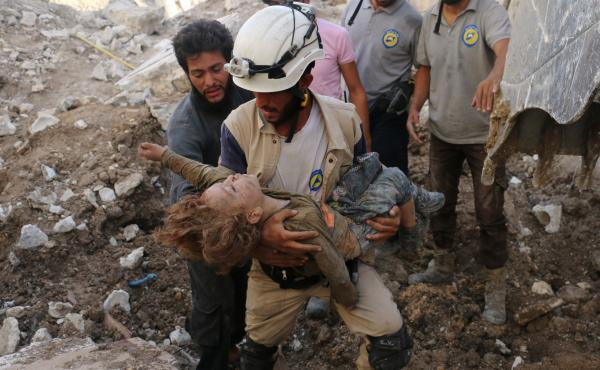 A Syrian civil defense volunteer, known as the White Helmets, holds the body of a child after he was pulled from the rubble following a government forces air strike on the rebel-held neighbourhood of Karm Homad in the northern city of Aleppo, on Oct. 4, 2
