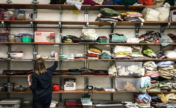 Betsy Jenson sorts through donated kitchenware, bed sheets and other household goods inside a storage area for the Nationalities Service Center in Philadelphia. The refugee resettlement agency uses donations to furnish apartments for newly arrived refugee
