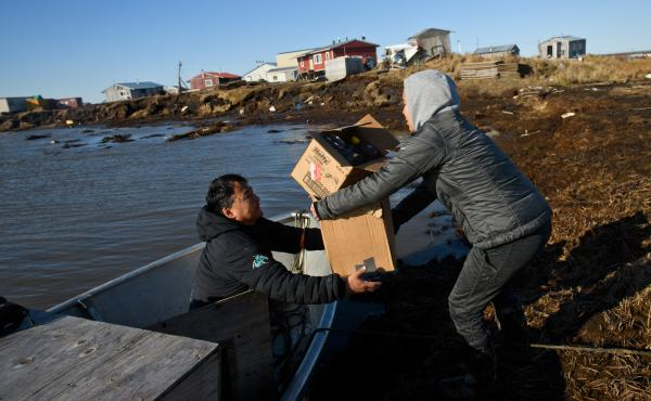 Harry Nevak (left) starts filling his boat in Newtok with his family's belongings in order to move them over to Mertarvik.