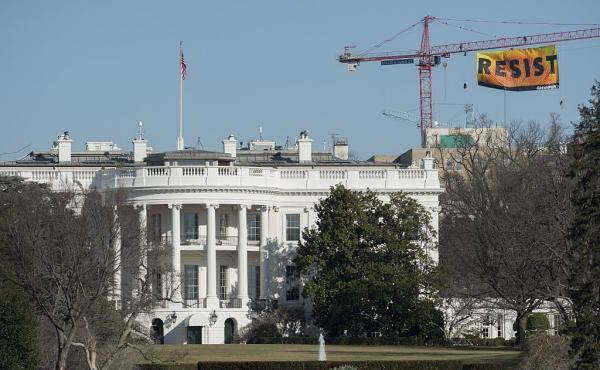 "Greenpeace protesters unfold a banner reading ""Resist"" from atop a construction crane on Wednesday behind the White House."