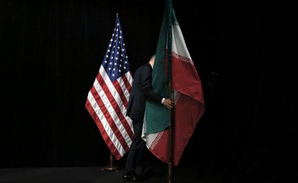 A staff person removes the Iranian flag from the stage after a group picture with representatives of the United States, Iran, China, Russia, Britain, Germany, France and the European Union during the Iran nuclear talks in July 2015 in Vienna.