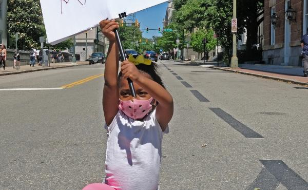Nasiah Morris, 4, of Richmond, carries a sign during a march from Brown's Island to the 17th Street Market in Shockoe Bottom, June 7. The youngster, kneeling at 9th and Grace streets across from the State Capitol, attended the rally with her mother, Toya