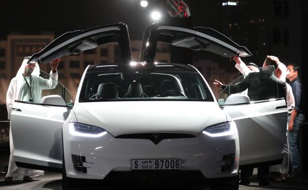 Emirati men check a Tesla vehicle during a ceremony in Dubai in February. The electric -vehicle maker recently announced the opening of a new Gulf headquarters in the United Arab Emirates.