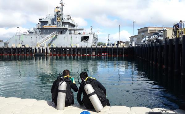 Two Chinese divers from the People's Liberation Army Navy are suited up and prepared to observe U.S. Navy divers in an underwater welding exercise.