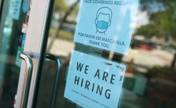 """A store in Miami displays a """"We are hiring"""" sign on March 5. U.S. employers added 916,000 jobs in March, the biggest number since August, amid an improving pandemic outlook and trillions of dollars in stimulus passed by Congress."""