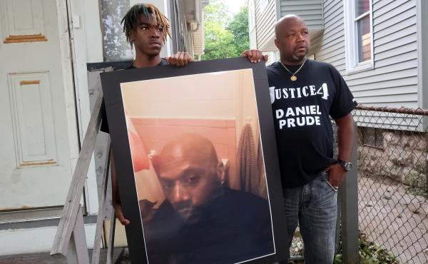 "Family members Armin Prude (left) and Joe Prude stand with a picture of Daniel Prude in Rochester, N.Y., Thursday, Sept. 3, 2020. While suffering a mental health crisis, Prude, 41, suffocated after police in Rochester put a ""spit hood"" over his head while"