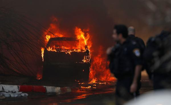 A vehicle burns outside a factory that was apparently hit with rocket fire Tuesday in the southern Israeli town of Sderot. Israel's military announced it had killed a commander of the Palestinian militant group Islamic Jihad in an early morning strike on