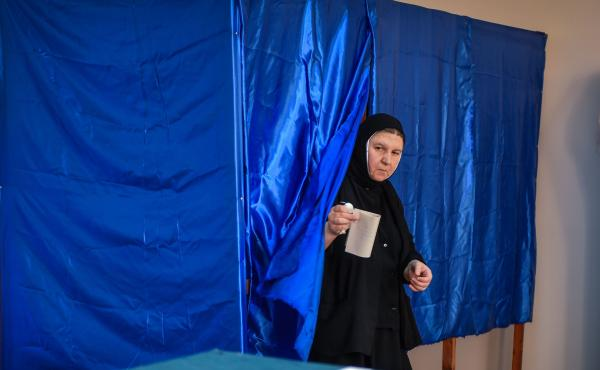 """A Romanian Christian-Orthodox nun votes at a polling station in the village of Branesti, Romania, in a referendum to change the constitutional definition of """"family"""", on October 6, 2018."""