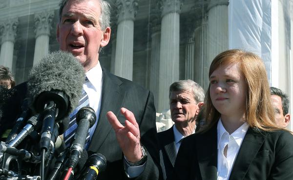 Attorney Bert Rein speaks to the media while standing with plaintiff Abigail Noel Fisher after the U.S. Supreme Court heard arguments in her case in 2012 in Washington, D.C.