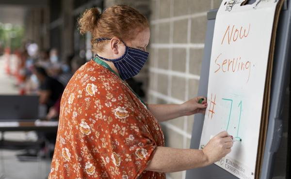 Vickie Gregorio with Heartland Workforce Solutions in Omaha, Neb., updates a whiteboard outside the workforce office as unemployed job seekers wait in line for help. A recent change in federal rules gives some people who have lost their health plan along