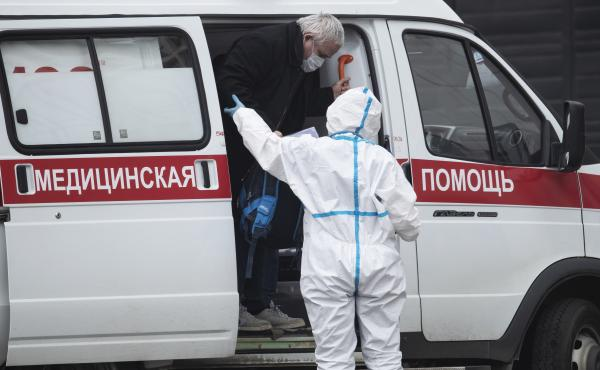 A medical worker helps a man suspected of infection with the coronavirus out of an ambulance at a hospital in Kommunarka, outside Moscow.