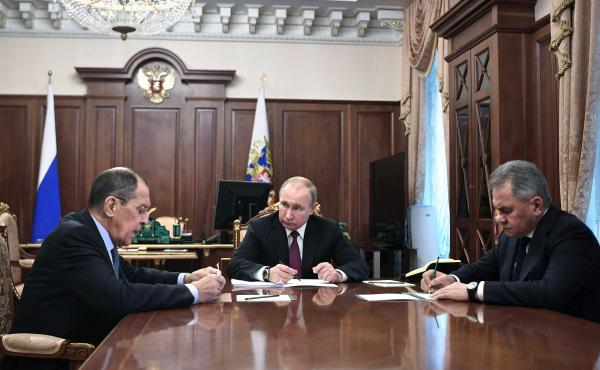 Russian President Vladimir Putin (center) attends a meeting with Russian Foreign Minister Sergey Lavrov (left) and Defense Minister Sergei Shoigu in the Kremlin in Moscow on Saturday. Putin said Russia would abandon the 1987 Intermediate-Range Nuclear For