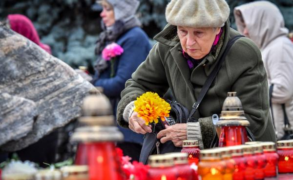 A woman places flowers at the Solovetsky Stone monument in front of the former KGB headquarters in central Moscow on Monday. Dozens of people gathered there to remember the victims of Soviet-era political repressions.
