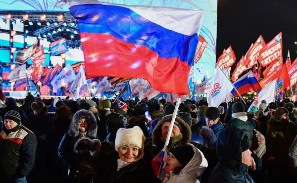 People attend a rally and a concert celebrating the fourth anniversary of Russia's annexation of Crimea at Manezhnaya Square in Moscow on Sunday. The controversial move to take Crimea became a proud event for some voters who handed Vladimir Putin a broad