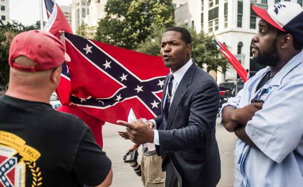 Jalaludin Abdul-Hamid, a protester against the Confederate flag that flies outside the South Carolina Statehouse, speaks to a flag supporter Tuesday.