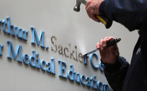 Tufts employee Gabe Ryan removes the Sackler family name from a building at Tufts University, the first major university to strip the Sackler name from buildings and programs.