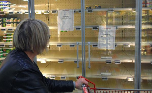 "A woman reads a sign that says, ""Due to a shortage of the raw material to make butter, we are not able to supply and sell you this product,"" attached to an empty refrigerated supermarket shelf in western France."
