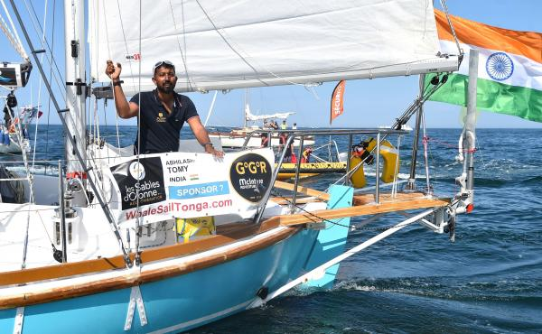 "India's Abhilash Tomy gestures on his boat Thuriya as he sets off from Les Sables d'Olonne Harbour on July 1 at the start of the solo around-the-world ""Golden Globe Race"" ocean race in which sailors compete without high technology aides such as GPS or com"