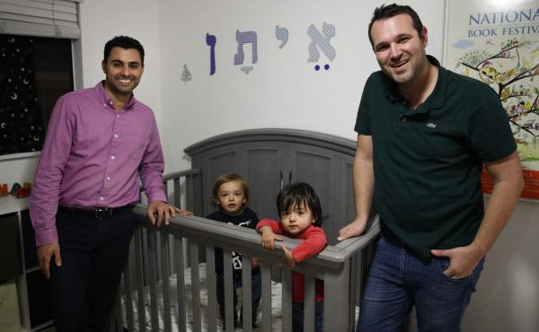 Elad Dvash-Banks (left) and his husband, Andrew, pose for photos with their twin sons, Ethan (right) and Aiden, in their Los Angeles apartment on Tuesday. Ethan is a plaintiff in a federal lawsuit against the State Department that seeks the same rights as