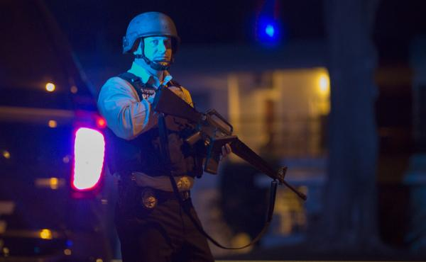 A policeman guards a police line late Wednesday as officers prepare to raid the home of one or more of the suspects in a mass shooting at the Inland Regional Center in San Bernardino, Calif.
