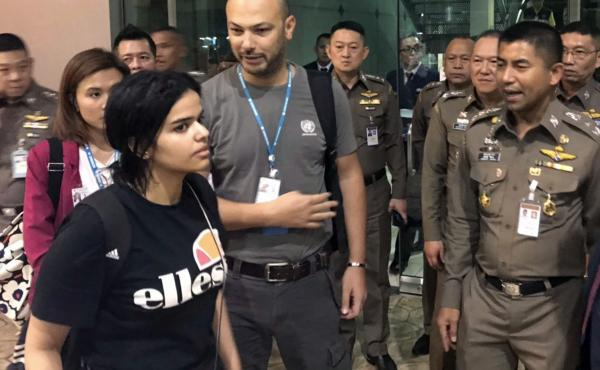 Saudi woman Rahaf Mohammed Alqunun walks by Thai Chief of Immigration Police Maj. Gen. Surachate Hakparn (right) before leaving the Suvarnabhumi Airport in Bangkok. Australia says it is considering granting refugee resettlement to the Saudi, who fled from