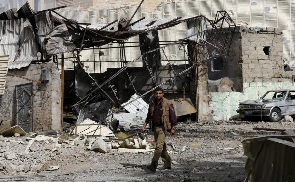 A man walks by a workshop damaged by an air strike on a nearby Scud missile base in Yemen's capital Sanaa in April.