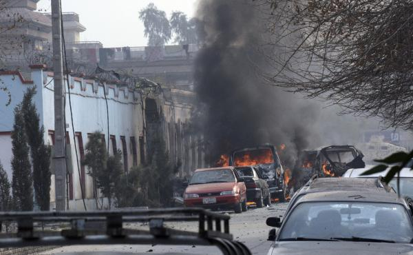 Vehicles burn after a deadly suicide attack in Jalalabad, east of Kabul, Afghanistan, on Wednesday. Gunmen then opened fire on the building.
