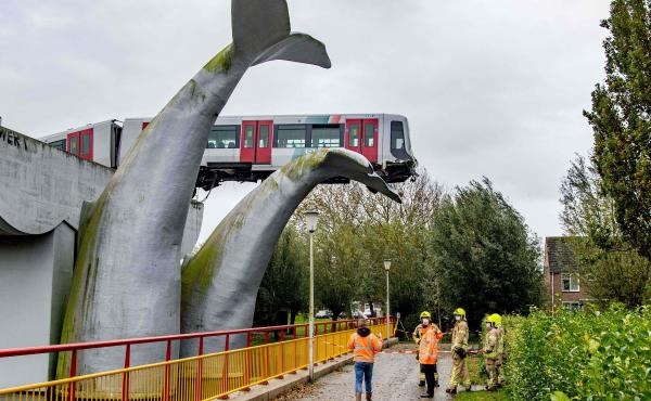 A massive sculpture of a whale's tail keeps a metro train aloft Monday after it shot through a stop block at De Akkers station in Spijkenisse, Netherlands. No injuries were reported.