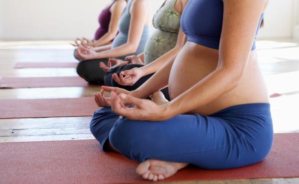 Four pregnant women sit in lotus position.