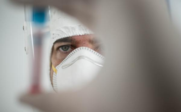 A researcher holds a tube containing the coronavirus.