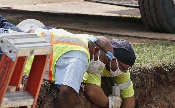 Workers reinforce the sides of an excavation site during the search for a potential unmarked mass grave from the 1921 Tulsa Race Massacre, at Oaklawn Cemetery in Tulsa, Okla., in July.