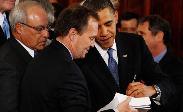 President Obama signs a copy of the Affordable Care Act for a member of Congress after signing the actual bill during a ceremony in the East Room of the White House on March 23, 2010, in Washington, D.C.