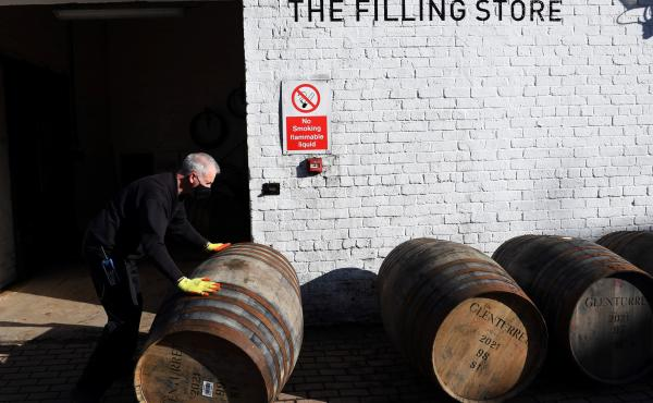 Scotch whisky producers are welcoming news of a breakthrough on tariffs, which came as the industry adjusted to both Brexit and then the COVID-19 pandemic. Here, an employee rolls a whisky barrel at the Glenturret Distillery in Crieff, central Scotland, l